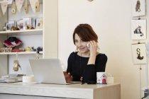 Frau sitzt am Schreibtisch und machen Anruf — Stockfoto