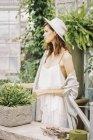 Frau mit Sonnenhut im Garten. — Stockfoto