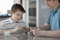 Мужчина и мальчик считают и обрабатывают наличные деньги . — стоковое фото