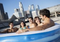 Friends in inflatable pool on a city rooftop — Stock Photo