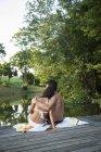 Мальчик и девочка, сидящие на деревянной пристани — стоковое фото