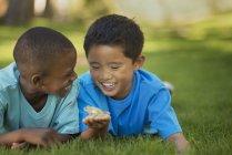 Chicos en la hierba sosteniendo una rana - foto de stock