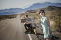 Couple on road in the desert hitchiking — Stock Photo