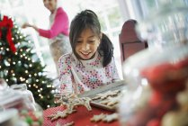 Girl decorating cookies with icing — Stock Photo