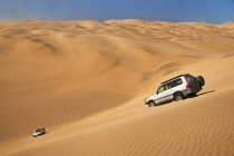 Off-road vehicles crossing sand dunes — Stock Photo