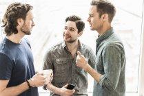 Three men standing talking — Stock Photo