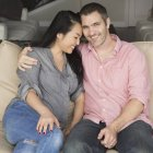 Smiling man and woman sitting on a sofa — Stock Photo