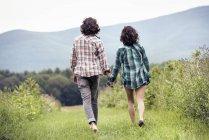 Mann und Frau gehen durch eine Wiese — Stockfoto