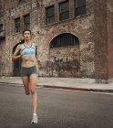 Mujer corriendo por un camino urbano - foto de stock
