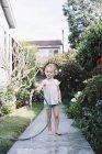 Jeune fille debout sur un chemin d'accès dans un jardin — Photo de stock