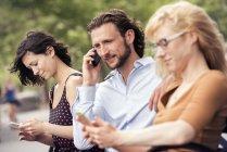 Homme et deux femmes sur leurs téléphones dans un parc — Photo de stock