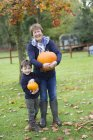 Woman and a small boy holding pumpkins — Stock Photo