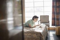 Femme couchée sur un lit dans une chambre de motel — Photo de stock