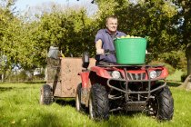 Man driving a quad bike and trailer — Stock Photo