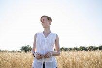 Junge Frau steht in einem Weizenfeld — Stockfoto