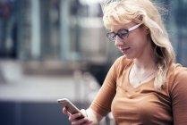 Femme dans une rue à l'aide de téléphone portable — Photo de stock