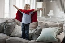 Bambino con le braccia sollevate una posa un supereroe — Foto stock