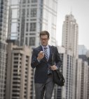 Businessman checking his phone on street — Stock Photo
