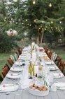 Длинный стол с тарелки и стаканы — стоковое фото