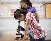 Двое детей с помощью микроскопа — стоковое фото