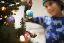 Young boy holding Christmas ornaments — Stock Photo
