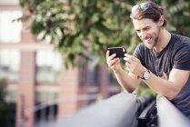 Людина, перевіряючи його мобільний телефон — стокове фото