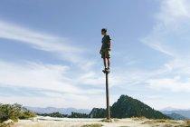 Man standing and balancing on metal post — Stock Photo