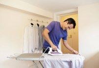 Man ironing a shirt — Stock Photo
