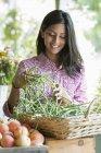 Femme portant des grappes de carottes — Photo de stock