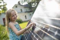 Девочка рядом с большой солнечной батареей — стоковое фото