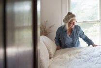 Mujer que compone la cama en el dormitorio - foto de stock