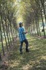 Homem andando por uma avenida de árvores — Fotografia de Stock