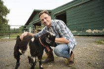Man with small goat on halter — Stock Photo