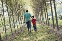 Homem e menino andando na avenida das árvores . — Fotografia de Stock