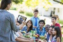 Взрослые и дети едят в саду. — стоковое фото