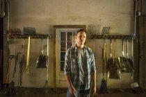 Homem de pé no celeiro com equipamento — Fotografia de Stock