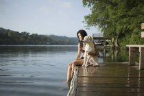 Woman with white dog on jetty — Stock Photo