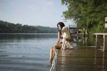 Frau mit weißer Hund auf Steg — Stockfoto