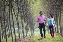 Casal caminhando entre árvores . — Fotografia de Stock