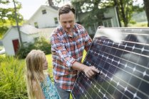 Father and daughter looking at a solar panel — Stock Photo