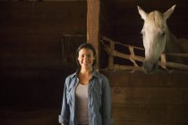 Woman standing in stable — Stock Photo