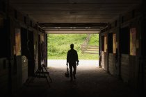 Man walking through stable — Stock Photo