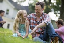 Father and daughter sitting on the grass. — Stock Photo