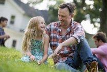 Padre e hija sentada en la hierba - foto de stock