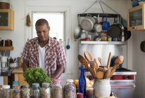 Uomo in una cucina che prepara insalata lascia — Foto stock