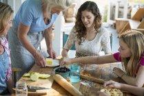 Frauen backen Plätzchen und Apfelkuchen. — Stockfoto