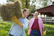 Men carrying hay on shoulders — Stock Photo