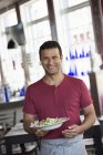 Male waiter serving a meal. — Stock Photo
