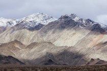 Cobertas de neve, montanhas e um céu ameaçador — Fotografia de Stock