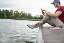 Человек, сидящий на пристани у озера — стоковое фото